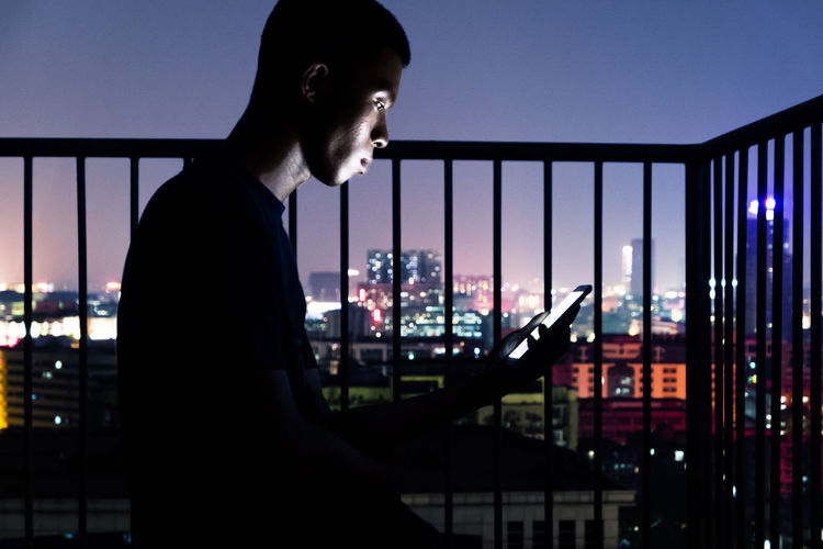 Side view of man using mobile phone while sitting in balcony against city at night