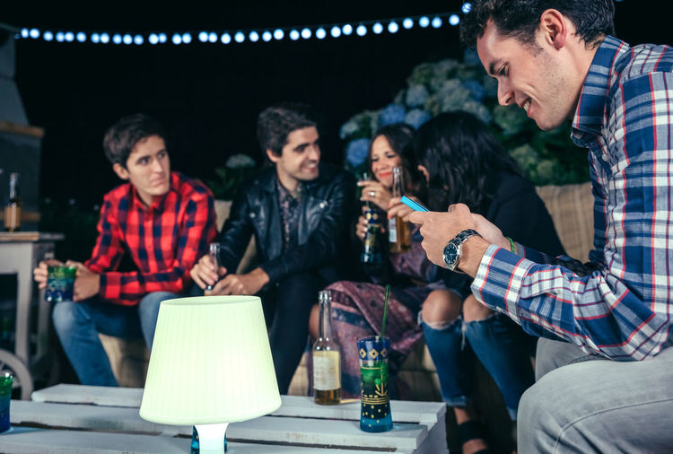 Portrait of happy man looking his smartphone in a outdoors party with friends. Friendship and celebrations concept. Celebration Friends Fun Happiness Happy Horizontal Young Alcohol Cheerful Drink Entertainment Friendship Group Group Of People Looking Night Nightlife Outdoors Party People Phone Photo Smartphone Smiling Sofa