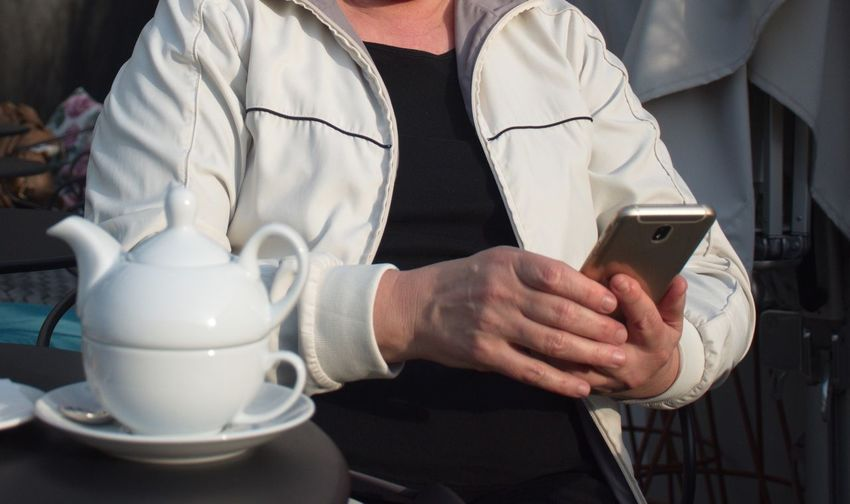 Midsection One Person Holding Real People Drink Mug Indoors  Clothing Close-up Occupation Communication Technology Phone Mobile Phone Mobile Device Texting Using Phone Kettle Table Cafe Working Woman Hands White