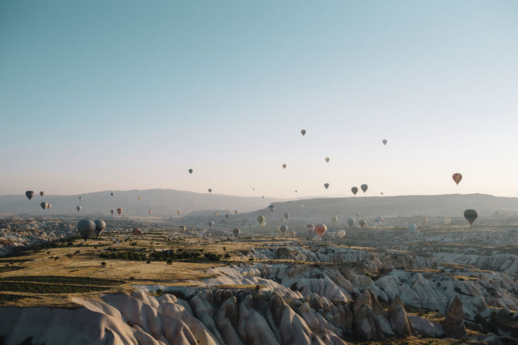 Hot air balloon flying over rocks against clear sky