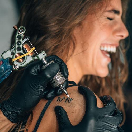 Close-up of mam making tattoo on woman back