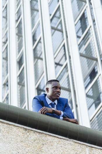 Full length portrait of young man sitting in building