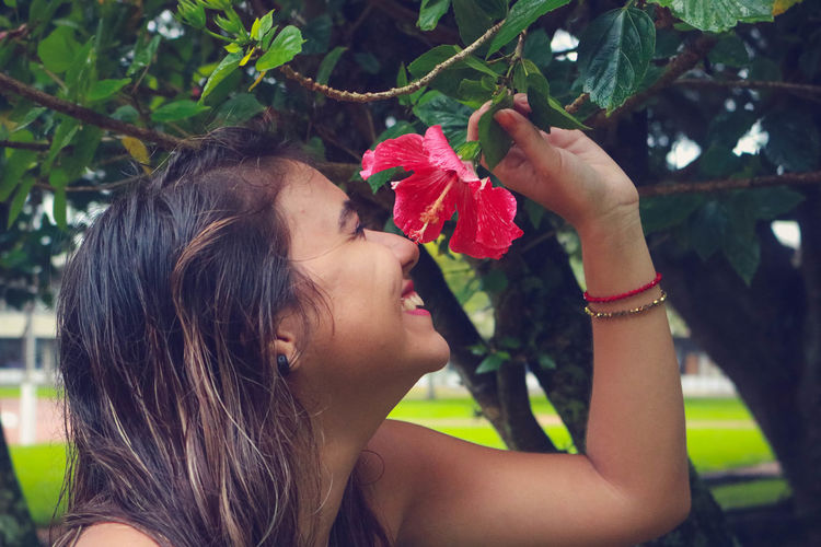 Smiling Young Woman Smelling Hibiscus Flower At Park