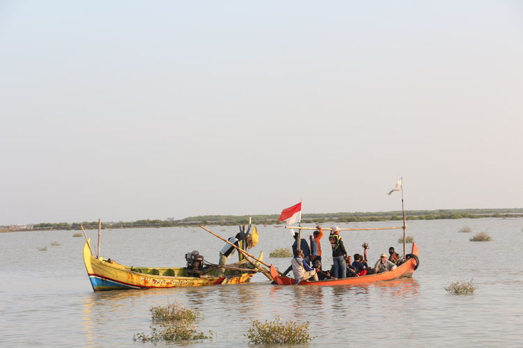 People on boat in sea against clear sky