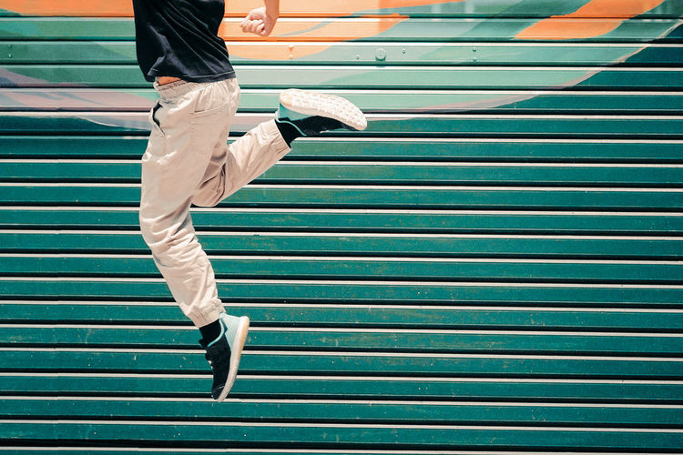 Low Section Of Man Jumping Against Metal Wall