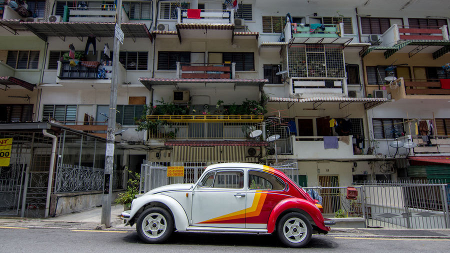 A classic VW Beetle parked in front of flats in a street in central Kuala Lumpur. A popular classic car to see in Malaysia. Cars Architecture Beetle Building Building Exterior Built Structure Car City Day House Land Vehicle Mode Of Transportation Motion Motor Vehicle No People Outdoors Railing Residential District Road Street Transportation Volkswagen