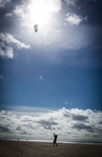 Man paragliding at beach against sky