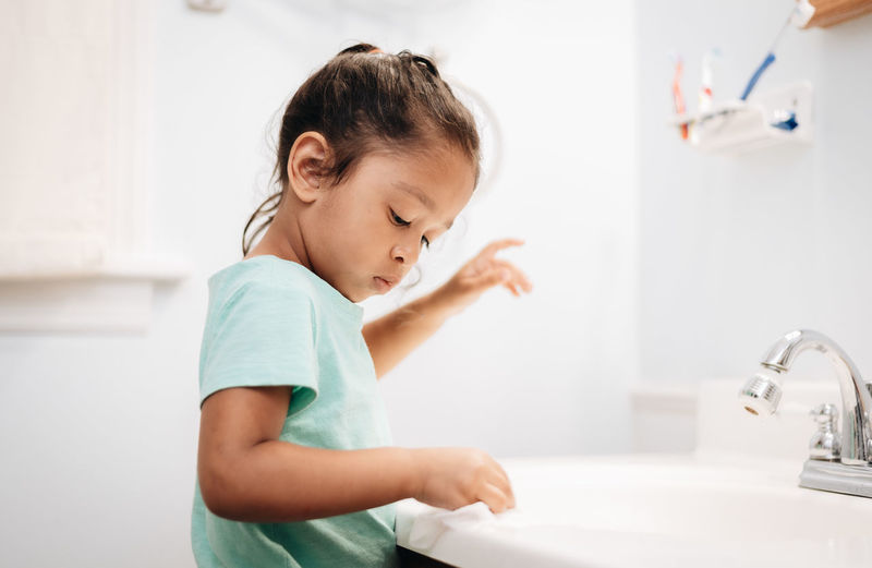 Cute girl washing napkin at sink