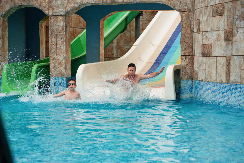 Boy with father enjoying on water slide