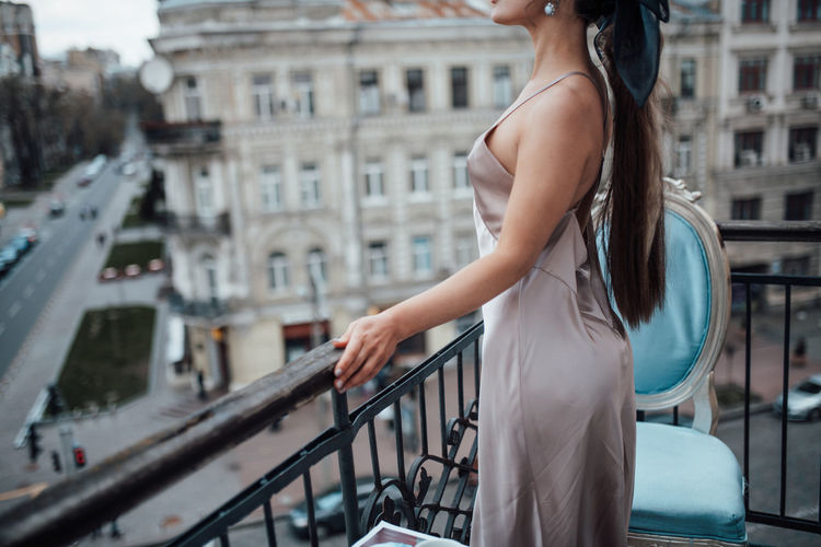 Midsection of woman standing by railing in city