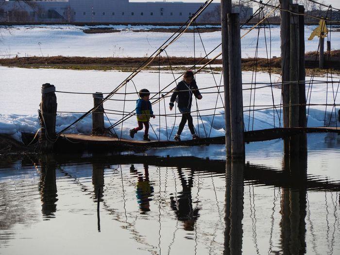 Sibling walking on footbridge over lake during winter