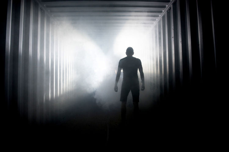 Rear view of silhouette man standing in fog