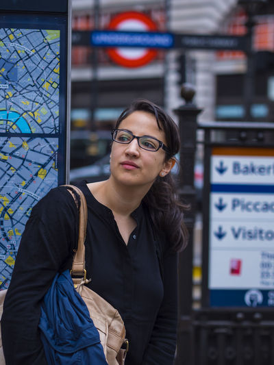 Woman looking away while standing in city