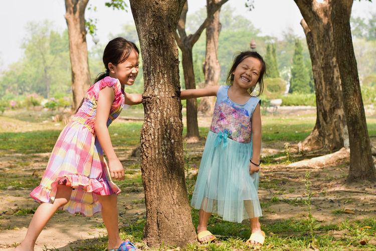 Full length of smiling girl on tree trunk