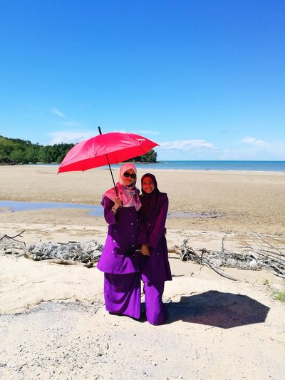 Woman with friend in traditional clothing holding umbrella at beach on sunny day