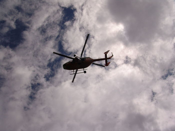 Low angle view of helicopter against cloudy sky