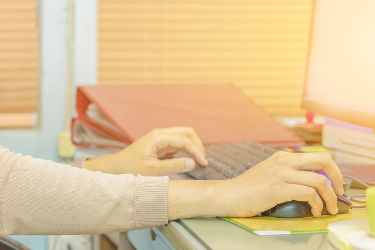 Cropped hands of woman using computer keyboard and mouse at desk