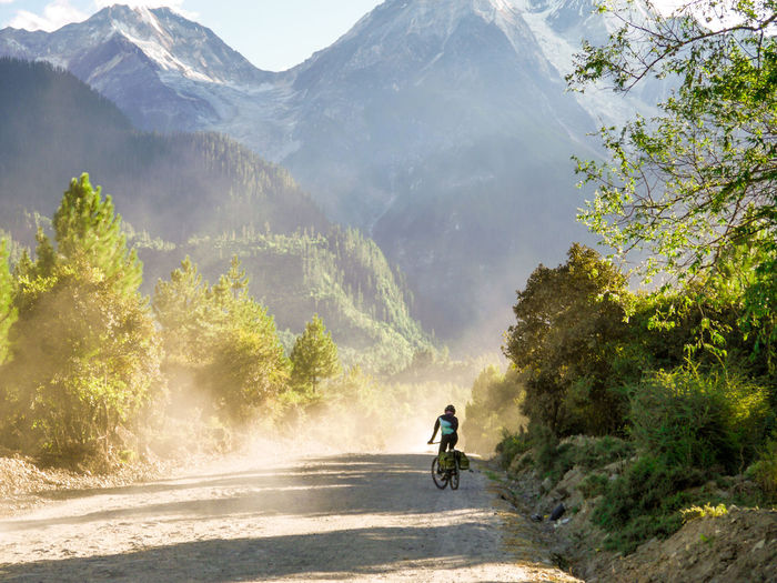 Man Riding Bicycle On Dirt Road Against Mountains