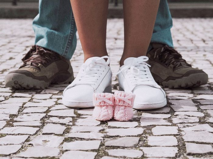 Low section of couple with baby shoes standing on footpath