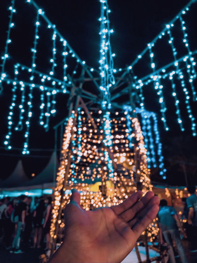 Cropped hand of person against illuminated christmas lights at night