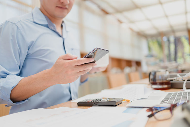 Midsection of businessman holding coffee cup using phone in office