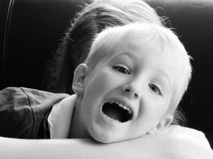 Portrait of cheerful boy with mouth open at home