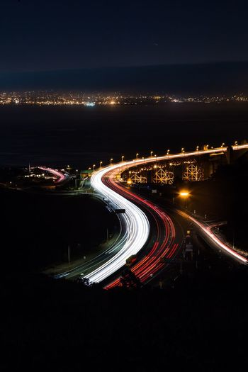 High angle view of light trails on road in city at night