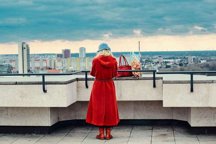 Rear view of woman in red against sky in city