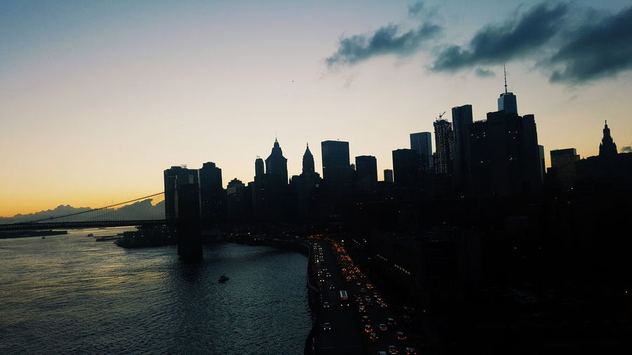 View of suspension bridge in city at dusk
