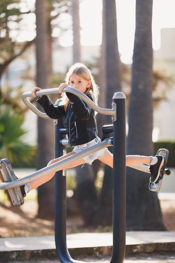 Full Length Of Girl Playing On Exercise Equipment In Playground