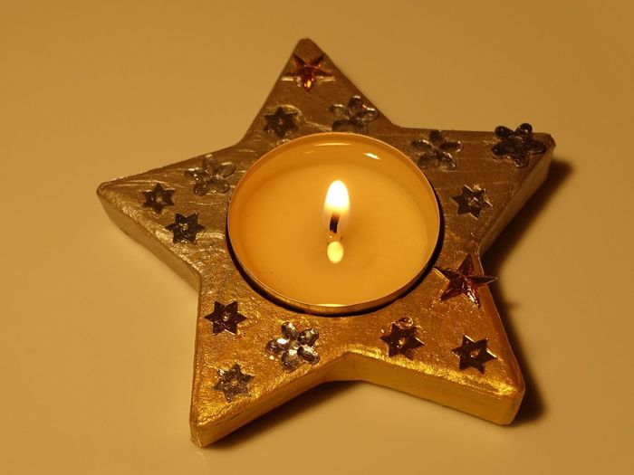 Close-Up Of Star Shape Tea Light Candle On Orange Background