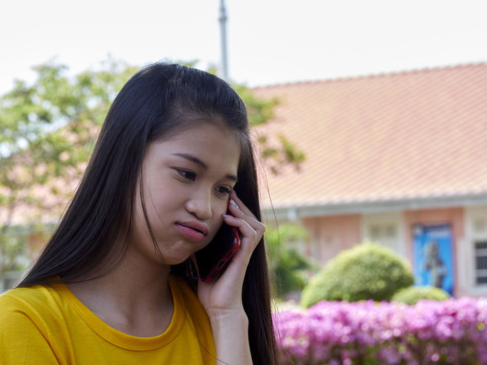 Close-up of girl talking on smart phone outdoors