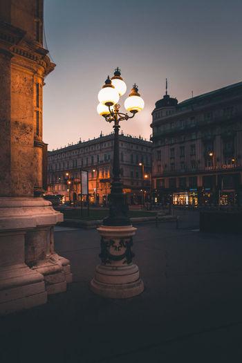 Illuminated street light in city at dusk