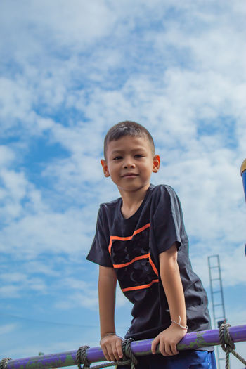 Portrait of cute boy standing by railing against sky