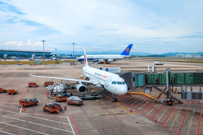 Air Vehicle Transportation Mode Of Transportation Airplane Airport Sky Cloud - Sky Airport Runway Travel Nature Day Passenger Boarding Bridge Commercial Airplane Outdoors Incidental People High Angle View Road Land Vehicle Aerospace Industry Water