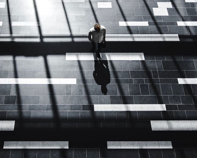 High angle view of woman walking on tiled floor
