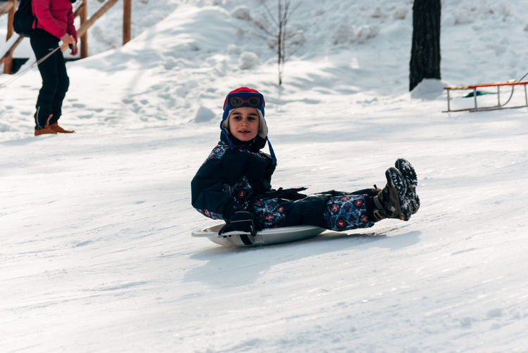 Boy Tobogganing On Snowy Field