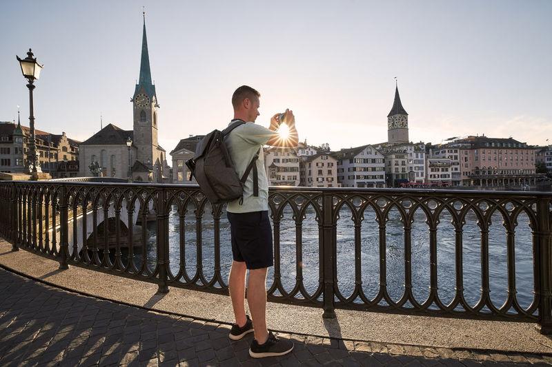 Full length of man standing on railing against buildings in city