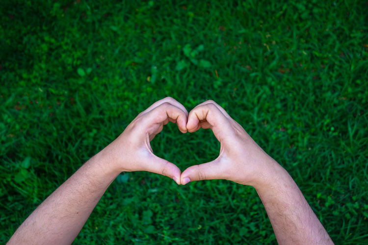 Cropped hands of man making heart shape over grassy field