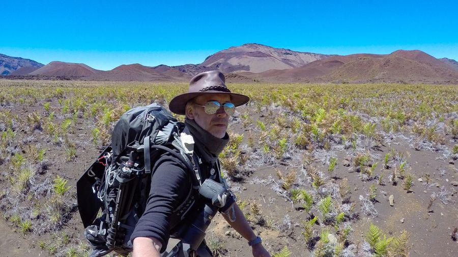 Portrait Of Hiker Walking On Landscape Against Clear Blue Sky At Haleakala National Park