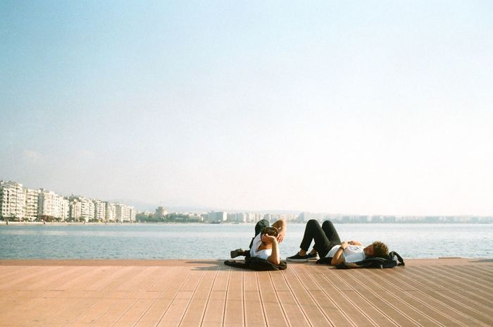 FRIENDS SITTING ON SHORE AGAINST SKY