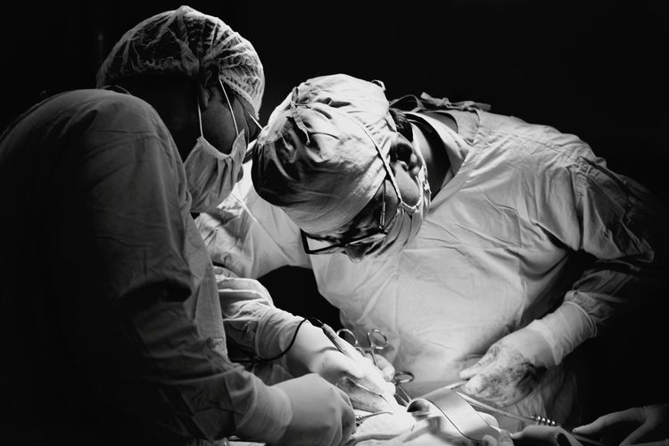 Surgeons Operating Patient Against Black Background