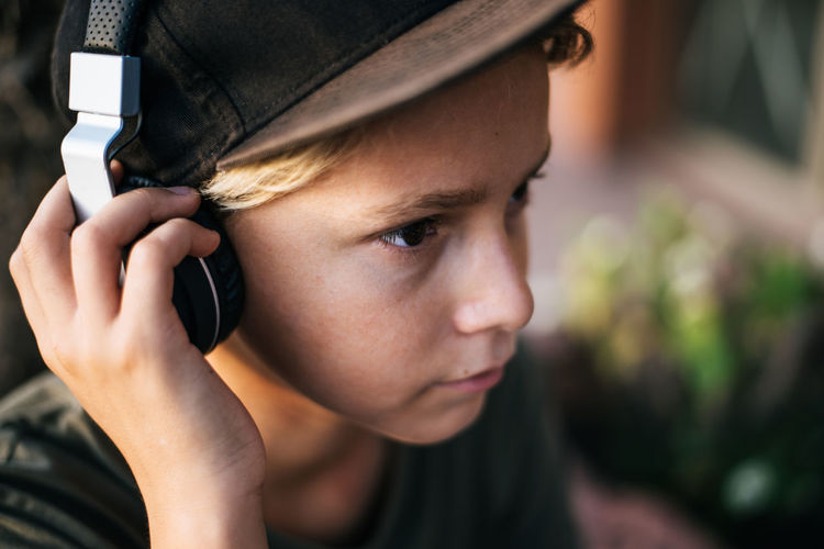 Close-up portrait of boy holding mobile phone outdoors