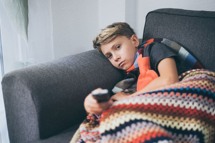 Portrait of ill boy watching tv while lying on sofa at home