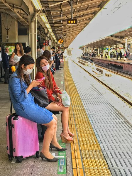 Waiting For A Train Sitting Wireless Technology Passenger Portable Information Device Communication Full Length Togetherness Public Transportation Journey Transportation Railroad Track Commuter Waiting Technology Railroad Station Platform Mobile Phone Subway Train Railroad Station People Adult