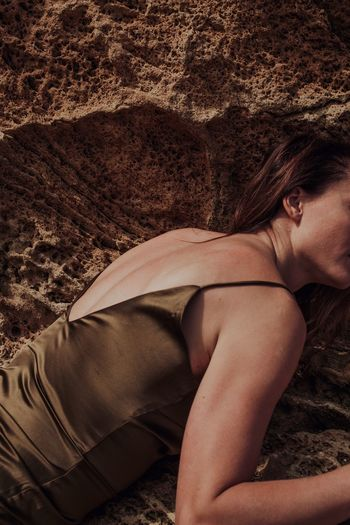 Midsection of woman lying on rock