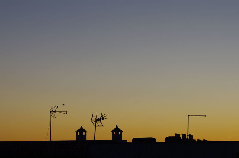 Low Angle View Of Silhouette Chimney And Antenna Against Clear Sky During Sunset