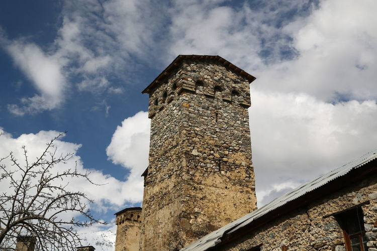Georgia Mestia/town In Svaneti/Georgia Sky Built Structure Cloud - Sky Architecture Low Angle View Building Exterior Nature Day No People History The Past Tower Building Old Stone Wall Outdoors Wall Tree Plant Stone Material