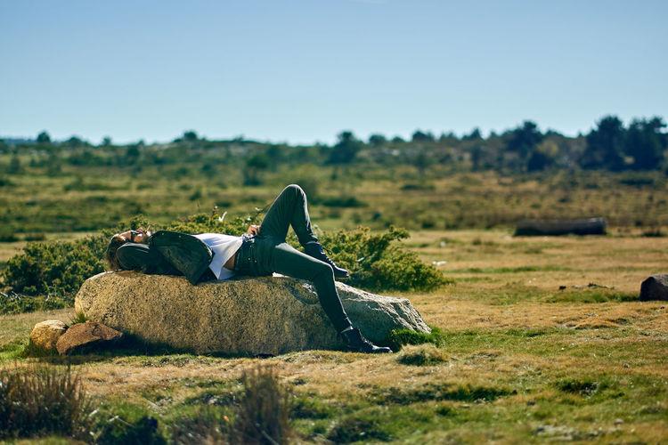 Man lying down on field against clear sky