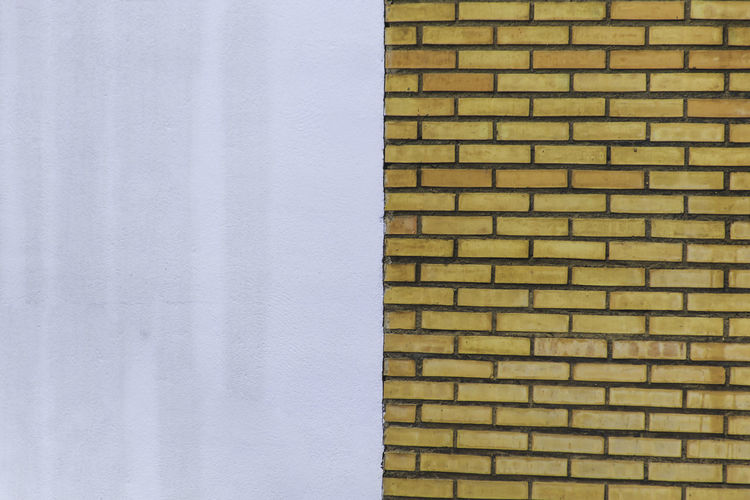 Division of facade Lines Architecture Backgrounds Brick Facade Brick Wall Building Exterior Built Structure Close-up Day Facades Full Frame Half No People Orange Bricks Outdoors Textured  Wall - Building Feature Wet Wet Facade White Facade Yellow Bricks